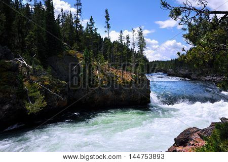 Yellowstone River gains momentum as it fast rapids culminates at the brink of Upper Falls in Yellowstone National Park. Photo is taken at the top of the falls.