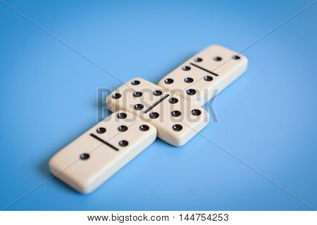 Domino parts, only showing number five over blue table. Selective focus