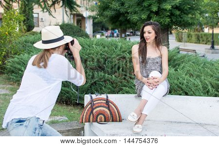 Two Friends Taking Pictures In Park