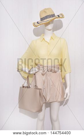 female yellow clothing with hat, ,bag on mannequin