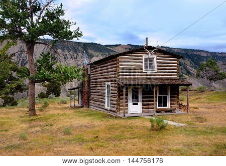 Early mail carrier's cabin sits in the area of Mammoth Springs in Yellowstone National Park. Cabin is two stories and sits on the edge of cliff.