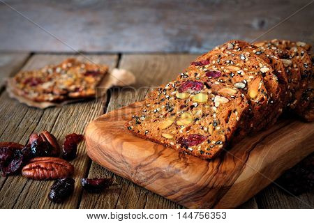 Baked Autumn Crispy Bread With Cranberries, Nuts And Seeds On Rustic Wooden Background