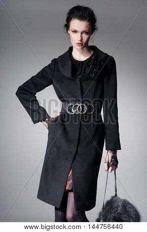 fashion girl in coat with handbag posing on light background