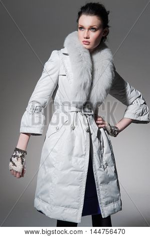 fashion girl in fur coat posing on light background