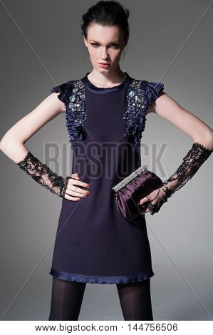 fashion model in gloves holding little purse posing-gray background