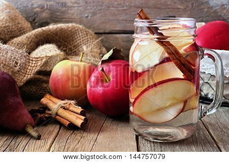 Autumn Themed Detox Water With Apple, Cinnamon And Red Pear In A Mason Jar. Scene On Rustic Wood Bac