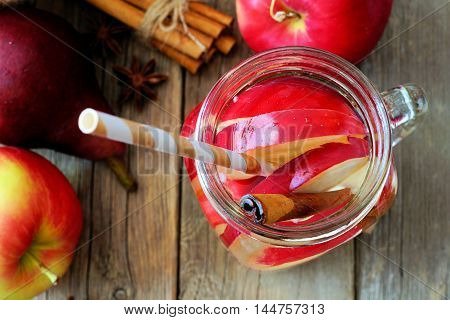 Autumn Themed Detox Water With Apple, Cinnamon And Red Pear In A Mason Jar Glass With Straw, Overhea