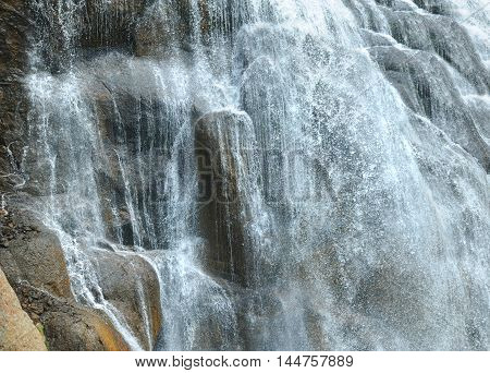 Base of Gibbon Falls on the Gibbon River in Yellowstone National Park splays across rocky ledges. Closeup of Falls.