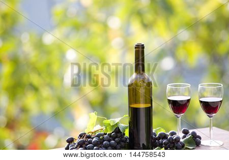 wine bottle and grapes on wooden table outdoor