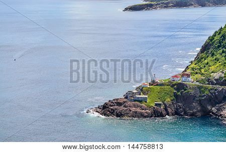 Boats motor past Fort Amherst.  Rugged coastline and Atlantic ocean. Warm summer day in August.  Views from atop historically famous Signal Hill in St. John's.  A speeding boat passing through appears slow relative to the vastness.