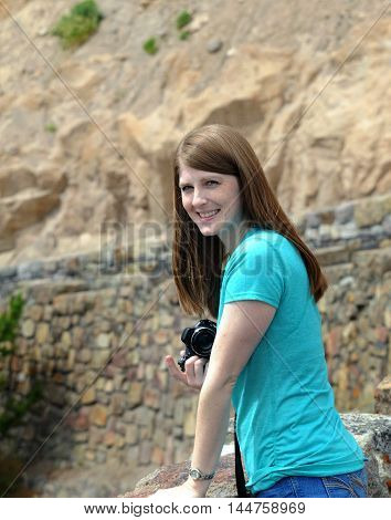 Attractive young woman photographs Gibbon Falls in Yellowstone National Park. she is smiling and holding a camera.