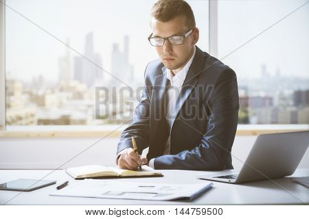 Handsome Young Man Writing In Notepad