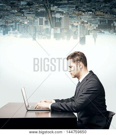 Businessman using laptop at desk on upside down city background