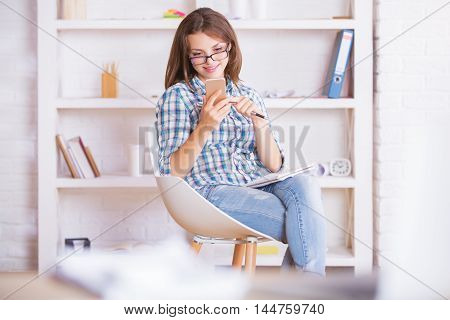 Businesswoman With Notepad Using Smartphone