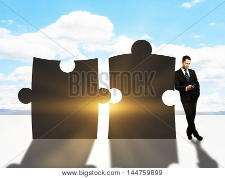 Businessman leaning on abstract giant puzzle pieces and using cellphone on sky background with setting sun