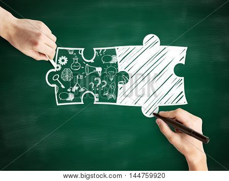 Male hands drawing puzzle pieces and success icons on chalkboard background. Business partnership sketch