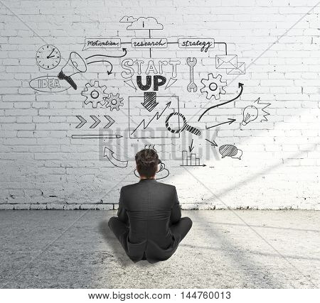 Startup concept with businessman sitting on concrete floor and looking at sketch drawn on white brick wall