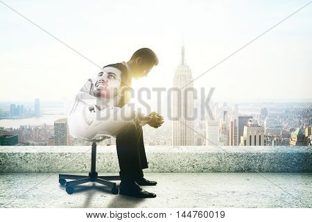 Young businessman thinking about vacation on rooftop with New York city view and sunlight. Man thinking about vacation