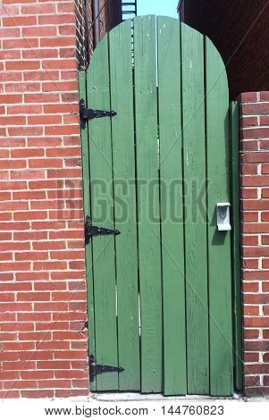 A rounded green door in a brick wall.