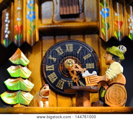 Cuckoo clock shows man sitting on a log drinking a bear while his dog keeps him company. Swiss chalet and clock piece in background.