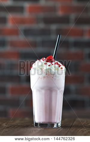 milk shake banana and raspberries with cream in a tall glass on a wooden background. Raspberry smoothie