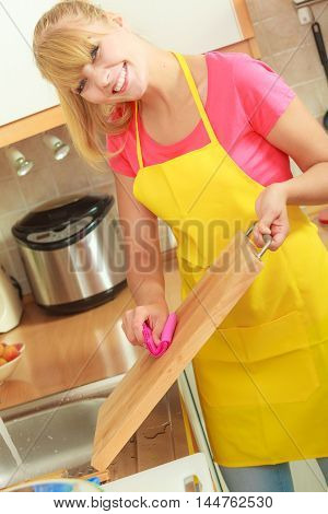 People housework and housekeeping concept. Woman doing the tidying up in kitchen cleaning wooden cutting board with rag sponge