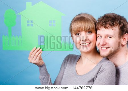 Romance feelings home finances concept. Youthful couple holding house symbol. Young boy with girl in love planning their future founding family.