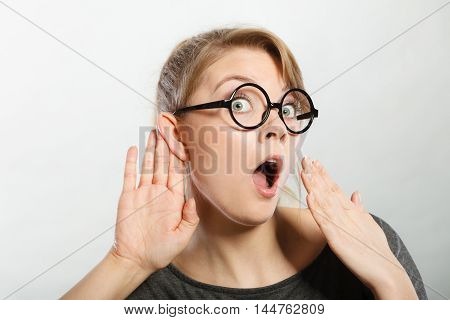 Hearing gesture shock emotion concept. Shocked girl eavesdropping. Young nerdy stunned lady in glasses listening expressing disbelief gasping.