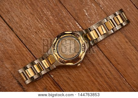 Mens hand watch on the wooden floor with a coin