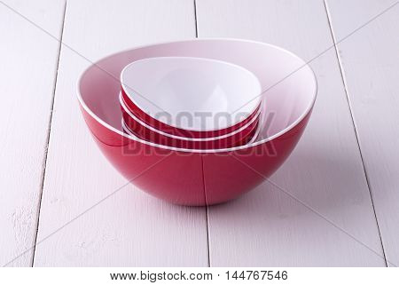 An empty red Salad Bowl and cups on a white wooden table