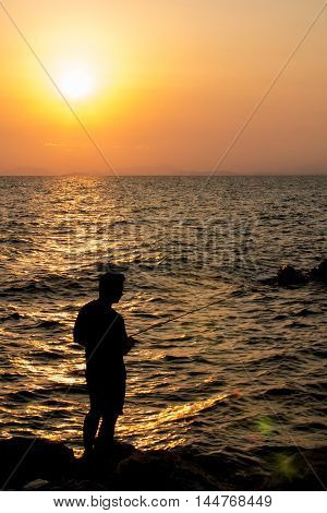 Fisherman fishing a perpon beside the sea.