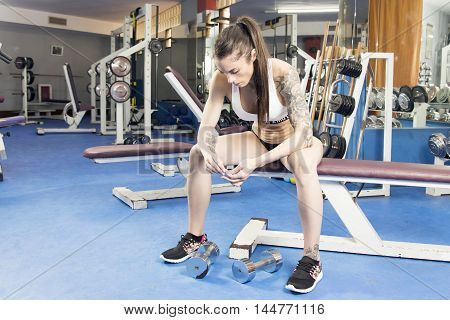 Woman Sitting On A Bench At An Old Gym.