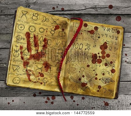 Alchemy book with bloody hand print and drops lying on wooden table. Halloween still life, black magic ritual with mysterious occult and esoteric symbols