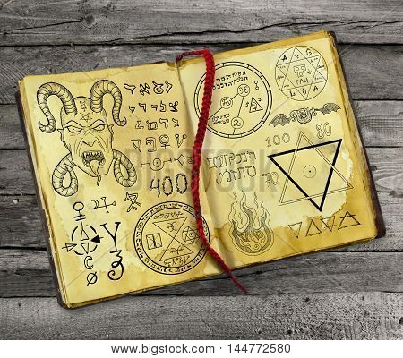 Old magic book with Devil, pentagram and mystic symbols lying on wooden table. Halloween still life, black ritual with occult and esoteric signs