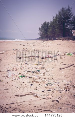 Pollution on the beach of tropical sea. Plastic garbage foam rubbish and dirty waste on beach in summer day. Clear sky on a bright sunny day outdoors at the daytime. Vintage tone effect.