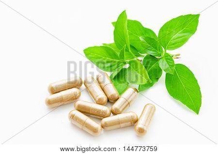 herbal drug capsule and green leaf on white background.