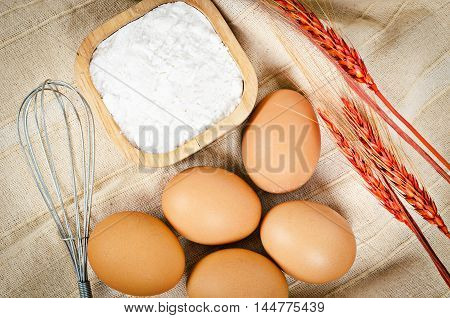 Eggs powder whisk with wheat on fabric background.