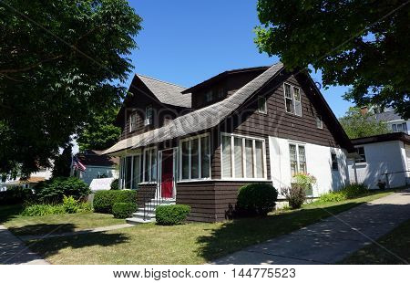 PETOSKEY, MICHIGAN / UNITED STATES - AUGUST 5, 2016: A two story brown home on Division Street, near downtown Petoskey, Michigan.