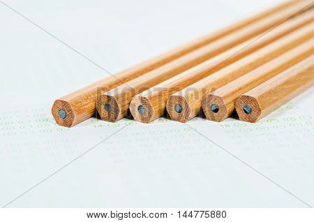 Wooden pencils on answer sheets or test paper background.