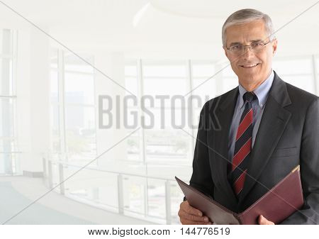 A mature businessman with a leather folder in a modern office building. The background is out of focus and high key. Horizontal format with copy space.