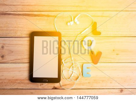 The Tablet And White Earphone With Love Alphabet On Wooden Background Among Sunlight In Warm Tone. M