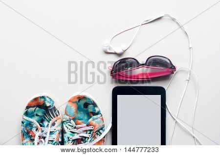 The Colorful Canvas Shoe, White Earphone With Sunglasses And Tablet On White Background. Accessories