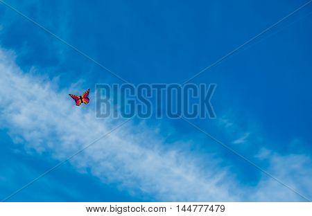 A kite that resembles a butterfly hovers in the blue sky.