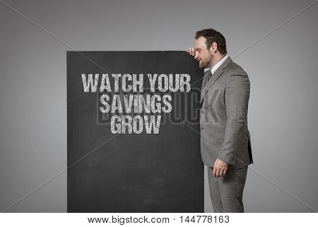 Watch Your Savings Grow text on blackboard with businessman standing side