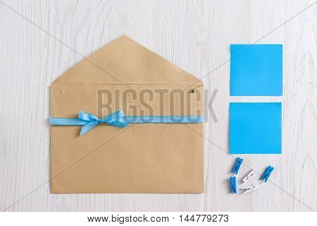 Brown envelope with blue ribbon and stickers on white wooden background, flat lay. Greeting card handmade set, blank paper. It's a boy note concept