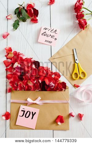 Making love message with envelope and rose petals, flat lay. Top view on workplace with paper, flowers, scissors and ribbon, white wooden background