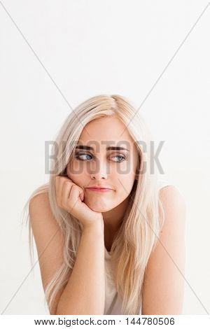 Beautiful woman with boring look, copy space. Pensive attractive blonde feeling disappointment, fatigue, boredom. White background