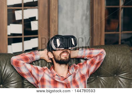 Man relaxing with virtual reality goggles, closeup. Bearded guy in vr glasses having rest and watching movies or video at home