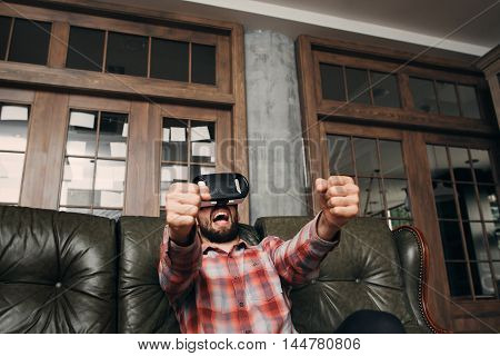 Guy watching sport game in 3d vr glasses. Sport fan just saw his favorite team won in virtual reality head set. Success, innovation, hobby, entertainment concept