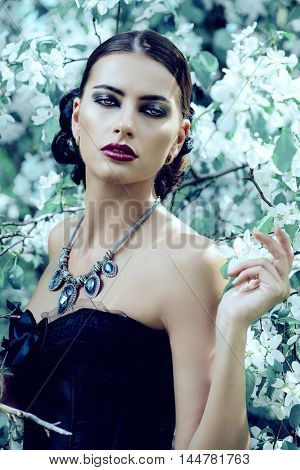 Beautiful brunette woman in long black dress posing in the blossoming forest. Medieval history, old times. Fashion. Gothic style.